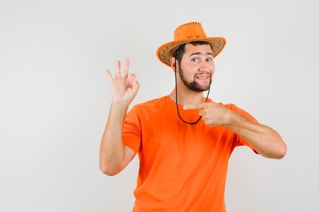 Молодой человек, указывая на свой знак ок в оранжевой футболке, шляпе и довольный, вид спереди.