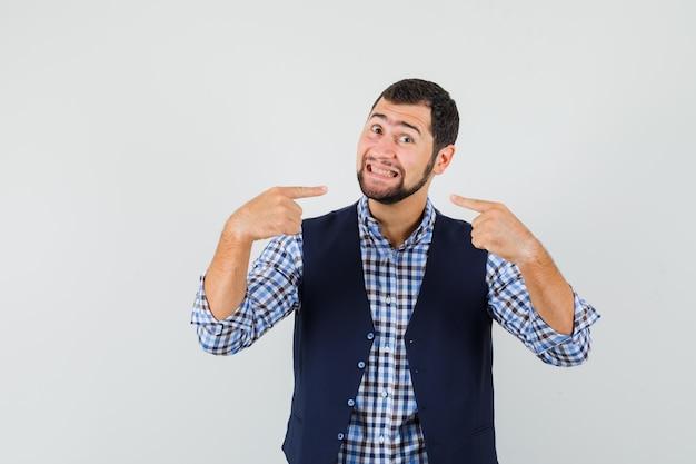 シャツ、ベスト、陽気に見える、正面図で彼の歯を指している若い男。