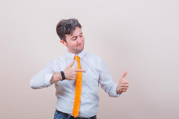 셔츠, 넥타이, 청바지에 자신의 엄지 손가락을 가리키고 쾌활한 찾고 젊은 남자