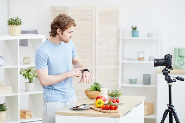 그의 시계를 가리키며 추종자를 위해 카메라에 건강한 식습관의 시간에 대해 말하는 젊은 남자