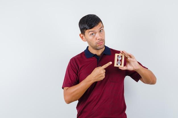 Молодой человек, указывая на песочные часы в футболке и глядя осторожно. передний план.
