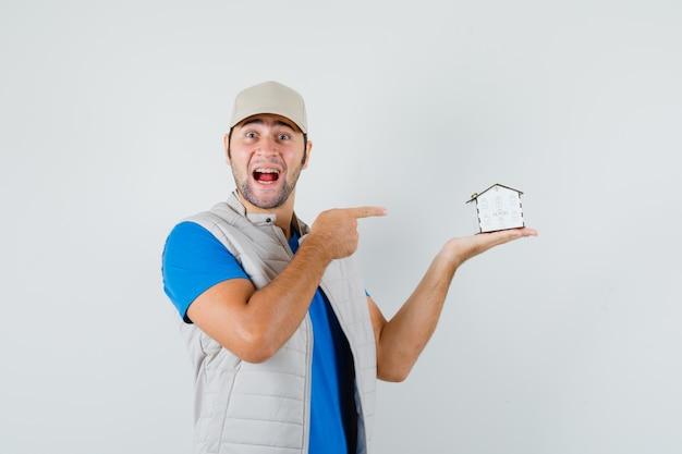 Tシャツ、ジャケット、キャップで家のモデルを指して、幸せそうに見える若い男、正面図。