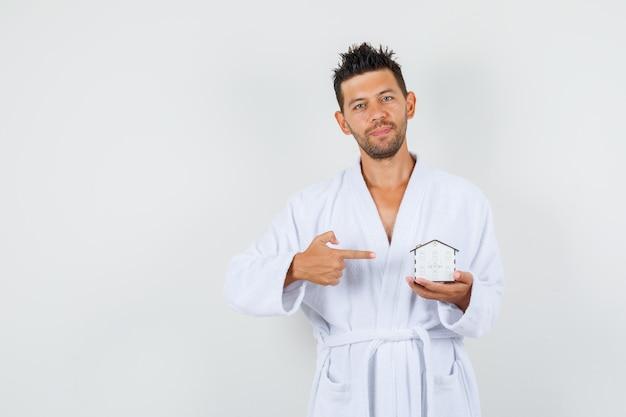 白いバスローブを着て家のモデルを指して、自信を持って見える若い男。正面図。