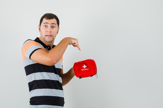 Молодой человек указывает на внутреннюю часть аптечки в футболке и выглядит взволнованным