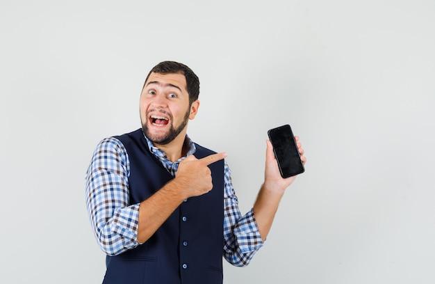 젊은 남자 셔츠, 조끼에 휴대 전화를 가리키고 행복을 찾고.
