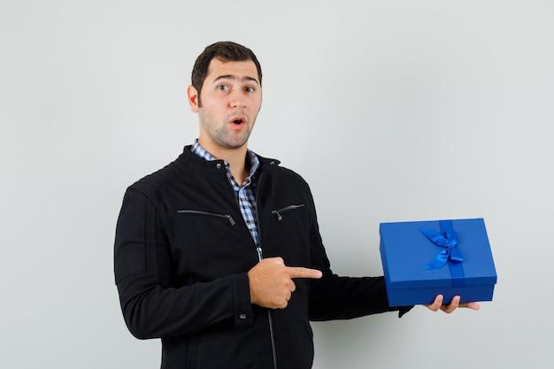 シャツ、ジャケットの現在のボックスを指して、驚いて見える若い男