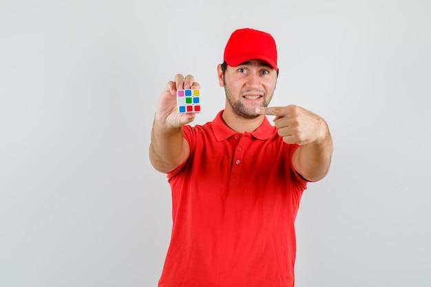 Молодой человек указывает на кубик рубика в красной футболке, кепке и выглядит довольным
