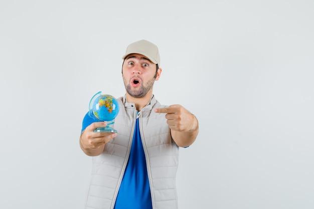Tシャツ、ジャケットで学校の地球を指して、驚いて見える若い男。正面図。
