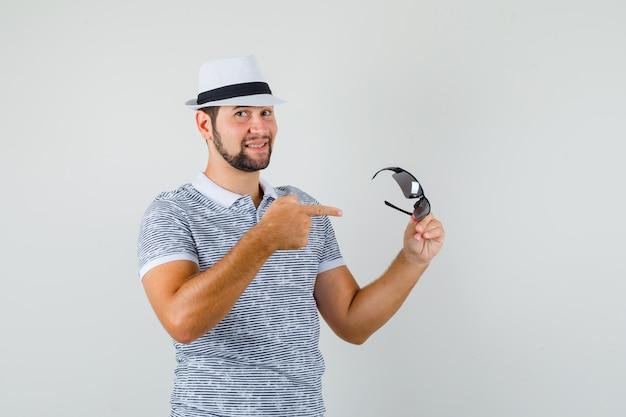 젊은 남자 t- 셔츠, 모자에 선글라스를 가리키는 기쁜, 전면보기.