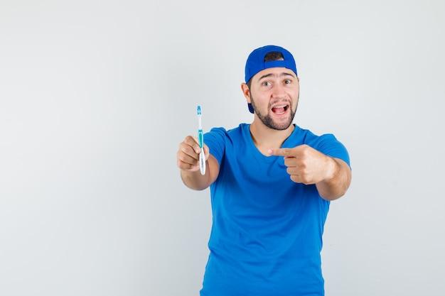 青いtシャツとキャップの歯ブラシを指して前向きに見える若い男