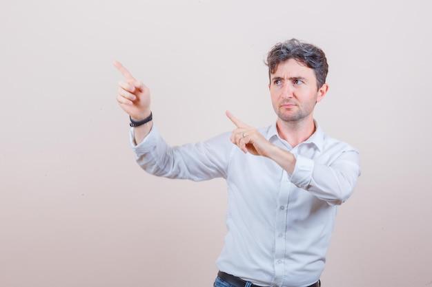 젊은 남자가 흰 셔츠, 청바지의 왼쪽 상단을 가리키고 초점을 맞춘 찾고