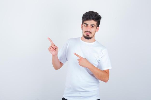白いtシャツで左上隅を指して自信を持って見える若い男