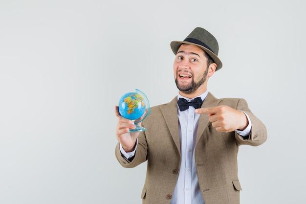 젊은 남자 정장, 모자에 세계 세계를 가리키고 명랑 한 찾고. 전면보기.