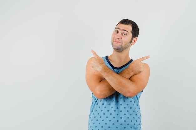 Young man pointing away in blue singlet and looking confident , front view.