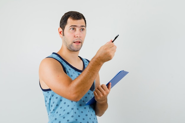 Young man pointing away, holding clipboard in blue singlet and looking puzzled. front view.