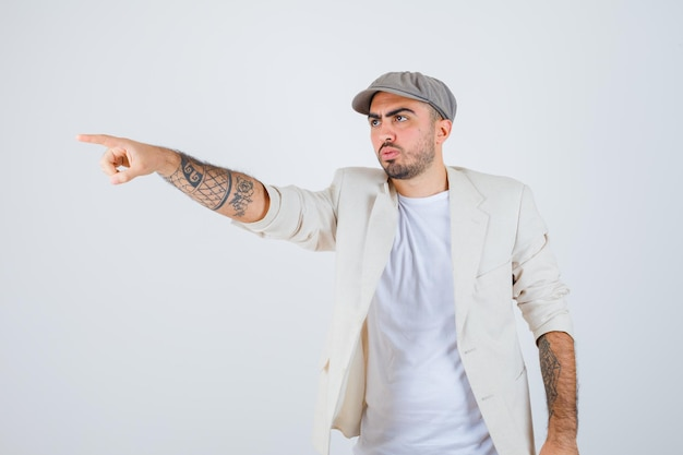 白いtシャツ、ジャケット、灰色の帽子を着て、真剣に見える若い男。正面図。