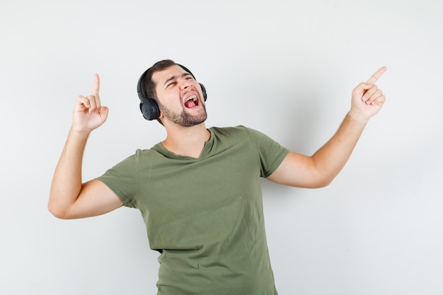 Young man pointing away while enjoying music in green t-shirt and looking energetic