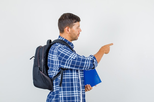 Young man pointing away while holding clipboard in shirt, backpack and looking focused .