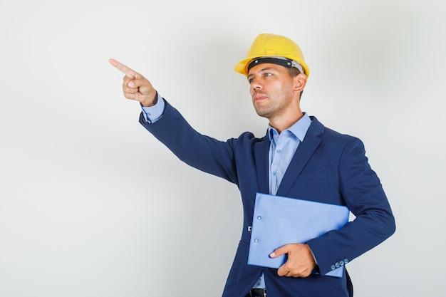 Молодой человек указывая в сторону с буфером обмена в костюме, защитном шлеме и выглядит занятым