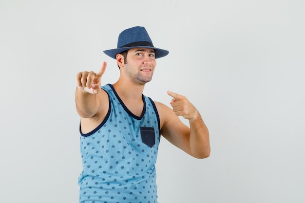 Young man pointing away with finger up in blue singlet, hat and looking confident. front view.