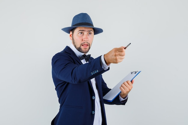 Young man pointing away with pen and holding clipboard in suit, hat front view.
