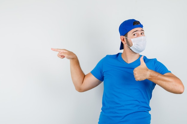 Young man pointing away with thumb up in blue t-shirt and cap and mask and looking pleased
