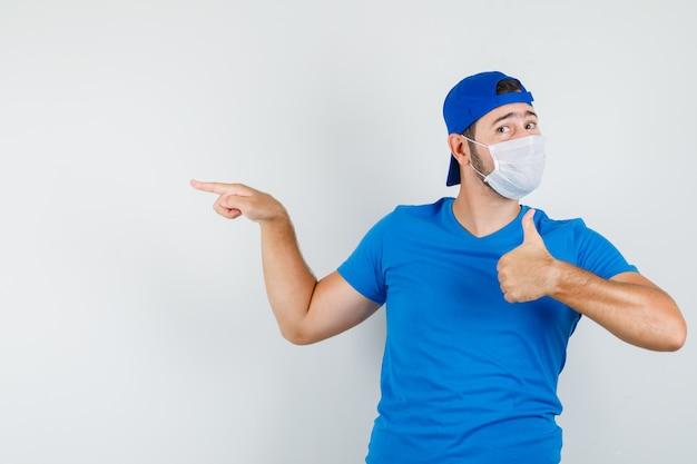 Молодой человек показывает пальцем вверх в синей футболке, кепке и маске и выглядит довольным