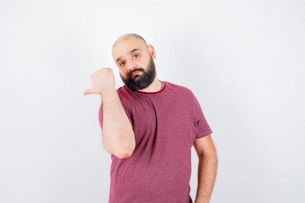ピンクのtシャツを振り返り、焦点を合わせて見ている若い男、正面図。
