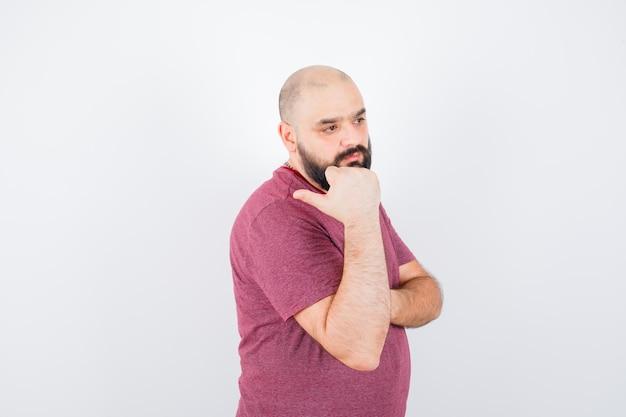 ピンクのtシャツで後ろを指している若い男。