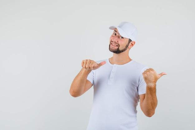 Молодой человек указывая назад в футболке и выглядел счастливым. передний план.