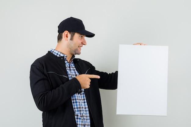Giovane che indica alla tela bianca in camicia, giacca, berretto e che sembra positivo.