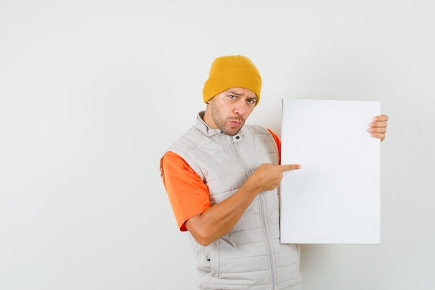 Giovane uomo che punta a tela bianca in t-shirt, giacca, cappello vista frontale.