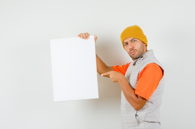 Giovane che indica alla tela bianca in t-shirt, giacca, cappello e che sembra serio. .