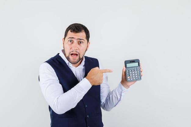 Giovane che indica alla calcolatrice in camicia, gilet e guardando perplesso