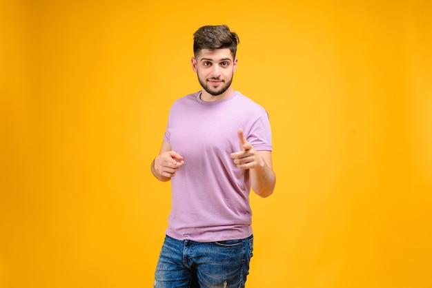 Young man pointing at camera isolated over yellow background