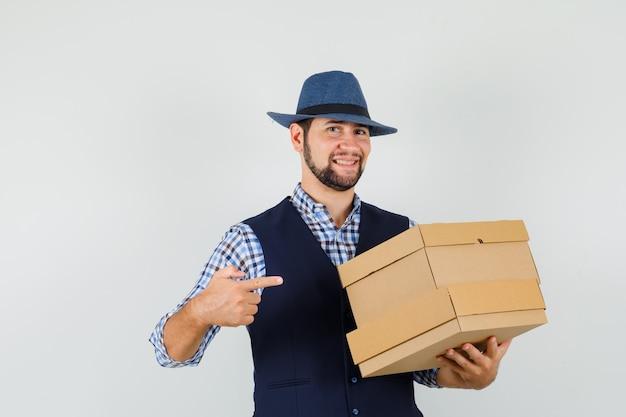 Giovane che indica a scatole di cartone in camicia, gilet, cappello e guardando allegro, vista frontale.