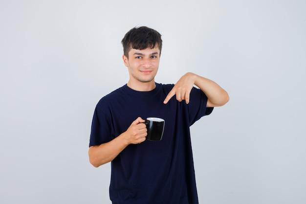 Giovane che indica alla tazza di tè in maglietta nera e che sembra fiducioso, vista frontale.
