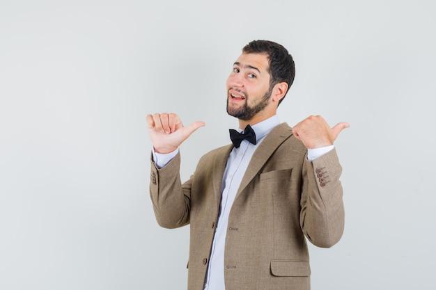 Молодой человек, указывая двойным пальцем вверх в костюме и выглядел уверенно. передний план.