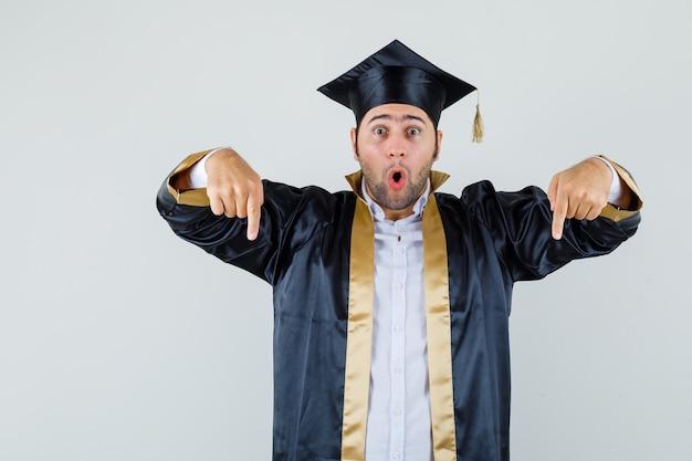 대학원 유니폼에서 아래쪽을 가리키고 놀란, 전면보기를 찾고 젊은 남자.
