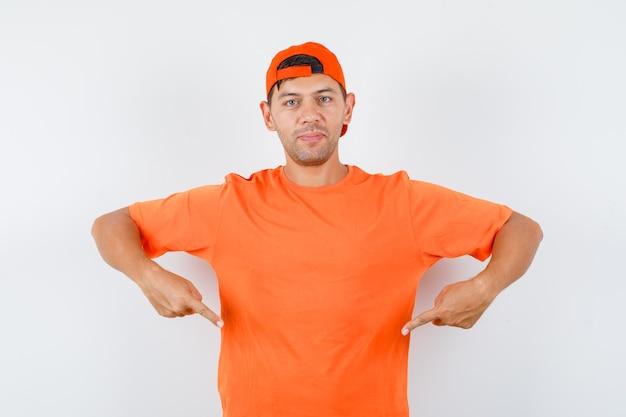주황색 티셔츠와 모자에서 아래쪽을 가리키고 자신감을 찾는 젊은 남자