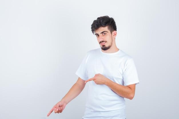 白いtシャツを着て、自信を持って見下ろしている若い男