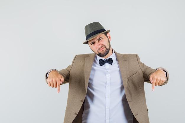 Giovane uomo rivolto verso il basso in tuta, cappello e guardando deluso. vista frontale.