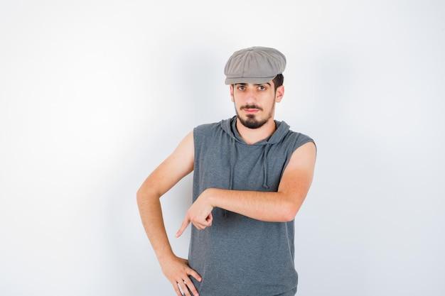 灰色のtシャツとキャップの人差し指で下向きに真剣に見える若い男