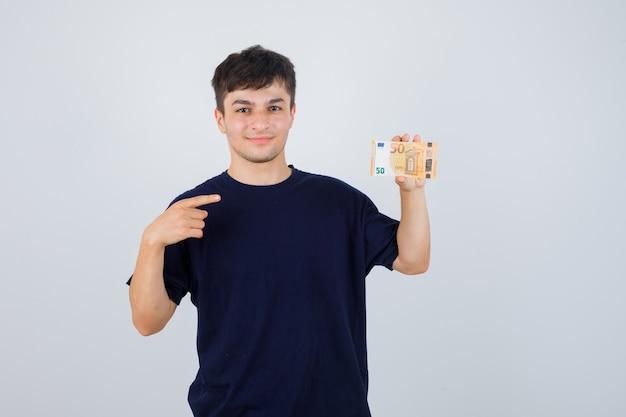 Giovane uomo che punta alla banconota in euro in maglietta nera e guardando fiducioso, vista frontale.