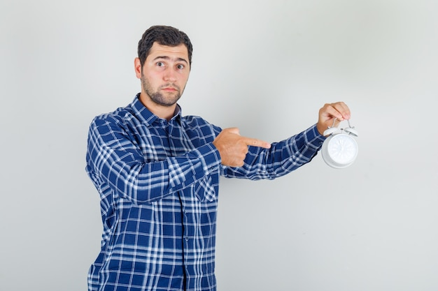 Young man pointing finger at alarm clock in checked shirt and looking worried.