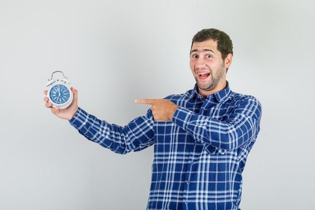 チェックシャツの目覚まし時計で指を指している若い男と興奮して探しています。