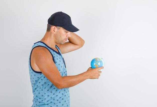 Молодой человек указывая пальцем на глобус в синей майке с кепкой и осторожно смотрит