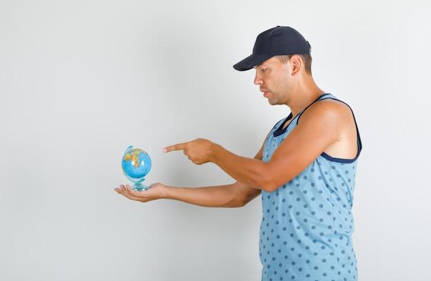 Молодой человек, указывая пальцем на глобус в синей майке с кепкой