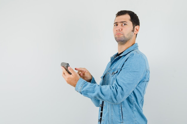 Young man pointing finger at calculator in t-shirt, jacket and looking serious. .