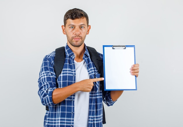 Young man pointing finger at clipboard in shirt, backpack and looking serious , front view.